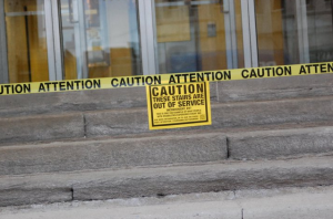 A staircase taped-off in London, Ontario's Central Business District.  The tape says Caution.