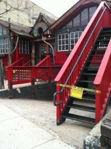 A red, steep, staircase taped-off in London, Ontario's Central Business District.  The tape says Caution.