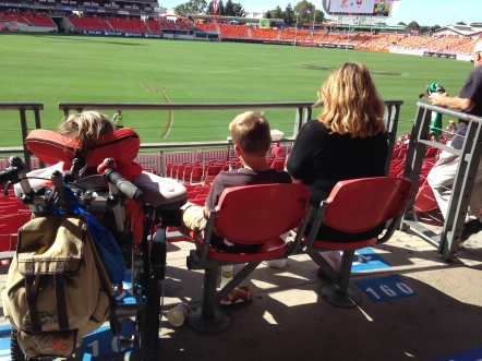 My son, Mac, sits with a friend and his mum, Gina, at an AFL football match in Sydney. In most instnaces, there is only an allocation of one spot for the person who uses the wheelchair and one other.
